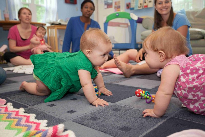 Babies crawling on the floor with moms watching